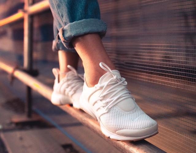 Person in blue jeans and white sneakers standing on metal 1858407