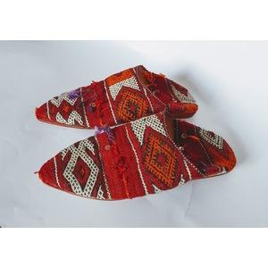 Babouche in tappeto berbero in tessuto con fondo rosso.