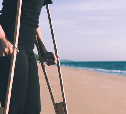 Patient woman using crutches support broken legs for walking at beach physical therapy concept t20 6ykgoy