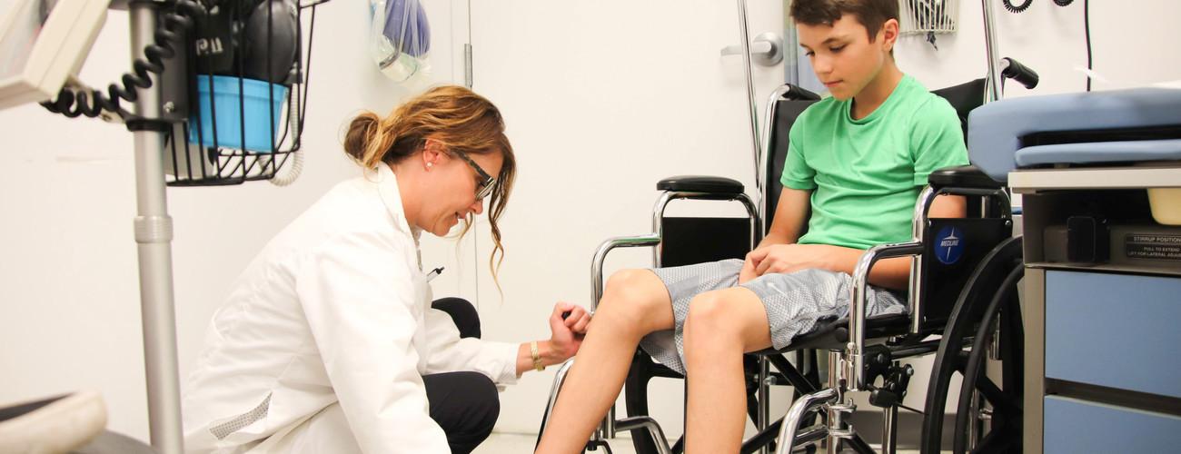 Nurse helping child with injured foot t20 yeg8wm