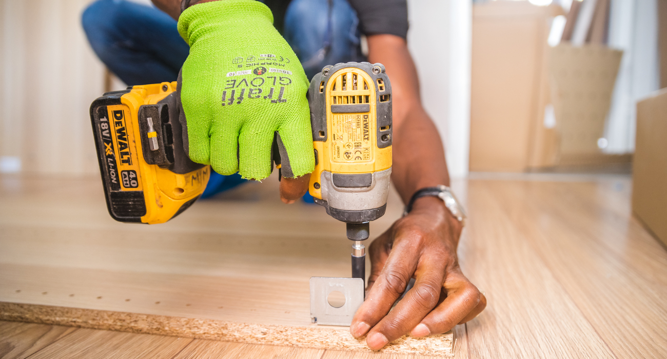 Person using dewalt cordless impact driver on brown board 1249611