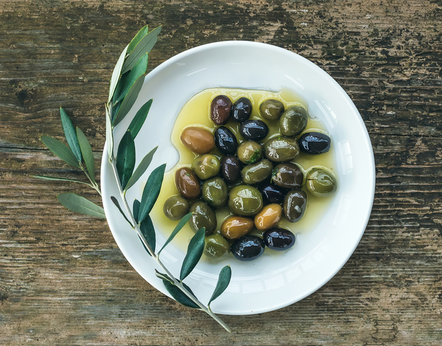 A plate of mediterranean olives in olive oil with  pxkvuzt