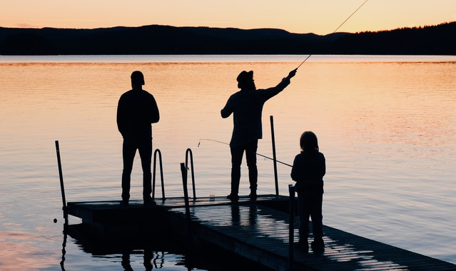 Three people on a wooden fishing docks 988622
