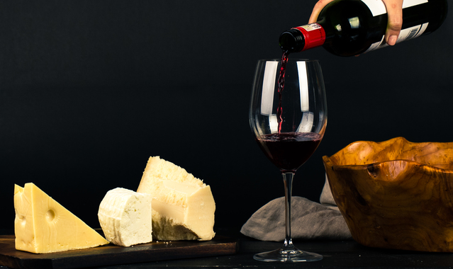 Photo of person pouring wine into glass besides some cheese 1545529