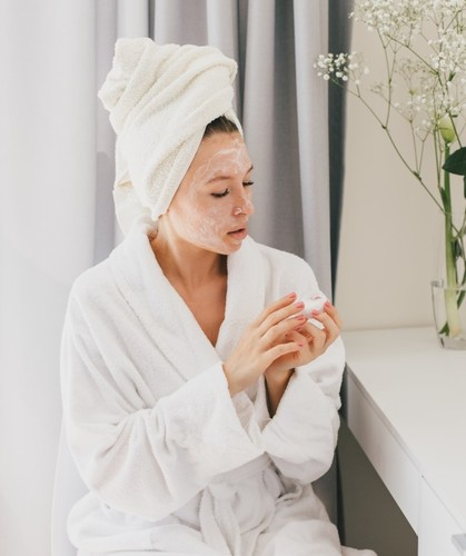 Woman wearing white bathrobe and towel on hair applying moisturizing cream on her face skin care t20 9knqr8