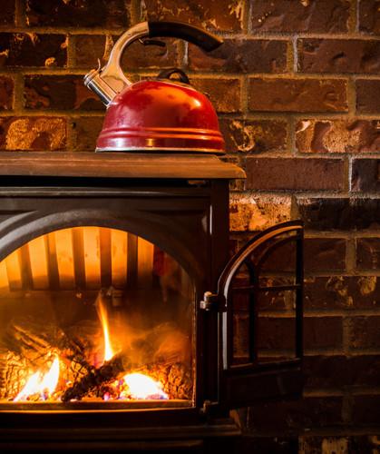Cozy warm fire heating a kettle against a brick hearth t20 py6ajp