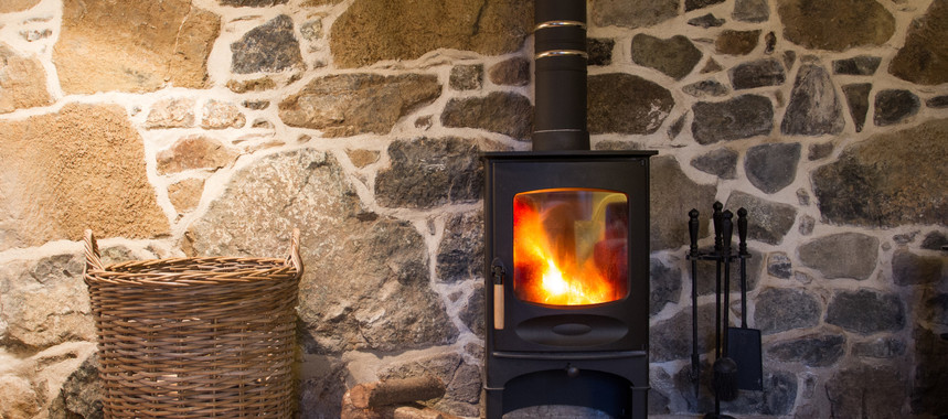 A wood burning stove and logs burning brightly in an old stone cottage t20 ggqm3m