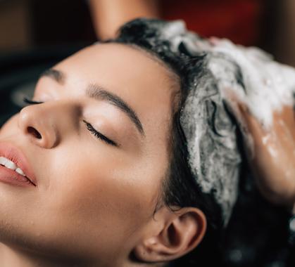 Hairstylist applying shampoo on womans hair 56879kl