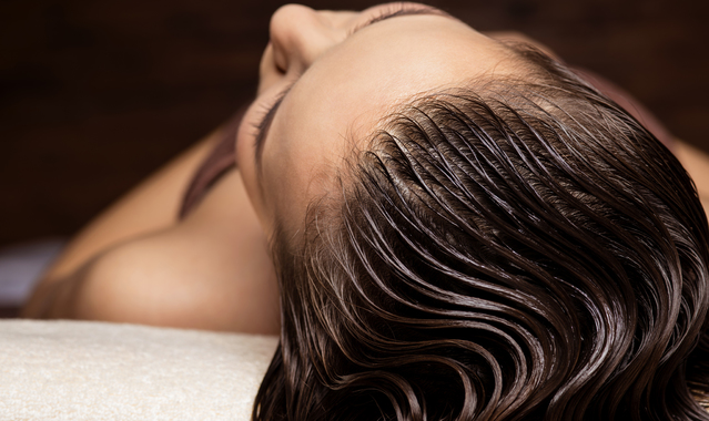 Woman receiving hair care procedure in spa salon u7eh5k6