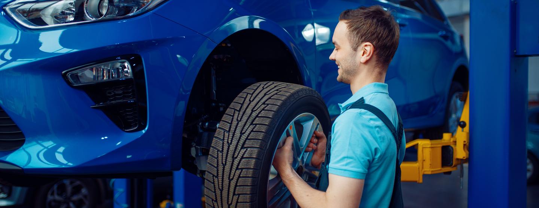 Worker removes wheel from vehicle car service aj7ke7r