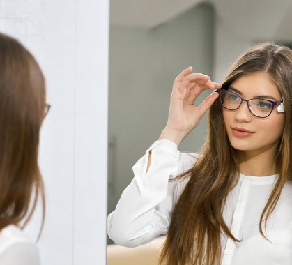 Young girl trying on eyeglasses in front of mirror wfx3qaq